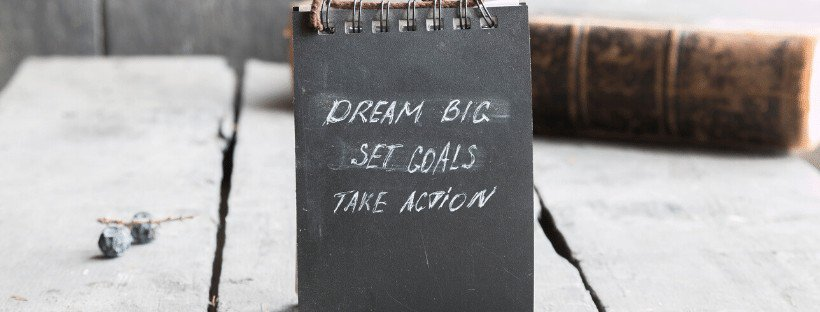 dream big set goals take action in chalk on chalkboard notebook