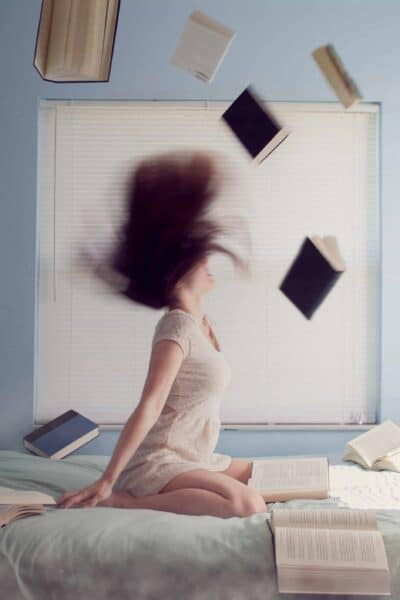 woman kneeling on bed with books in the air