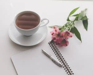 ournal with morning pages technique next to cup of coffee