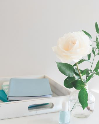 wooden box and rose in glass vase next to journals with letter writing techniques